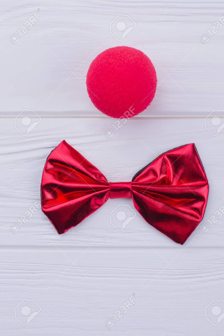Red clown nose sponge and bow-tie. Flat lay composition with party items on white wooden background. - 124508560