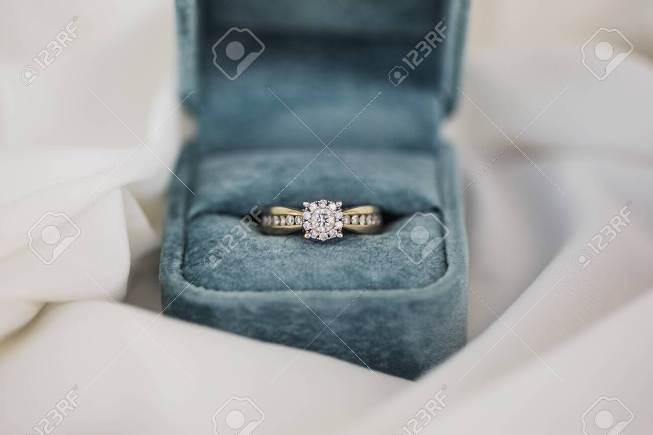 Gold wedding rings in box. Ring with diamonds - 123759025
