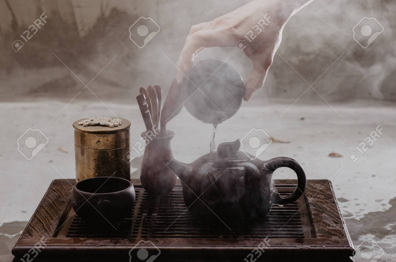 Cropped shot of woman pouring tea in traditional chinese teaware - 144389529