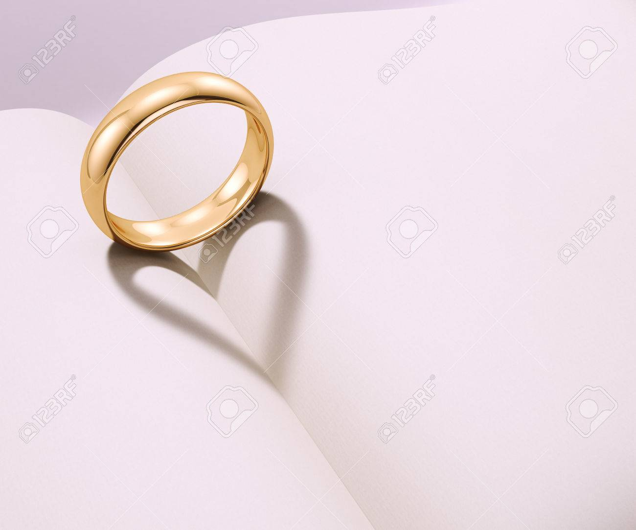 Wedding ring casting heart shaped shadow over a blank book - 51112440