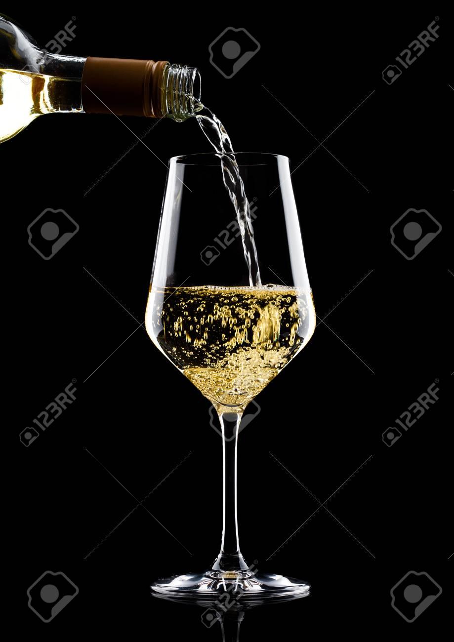 3eb3ccf6e3417d Gietende witte die wijn van fles aan glas op zwarte achtergrond wordt geïsoleerd  Stockfoto - 88792599