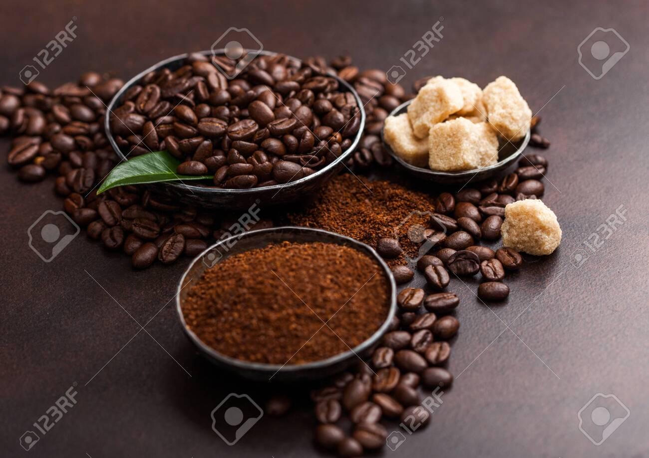 Fresh raw organic coffee beans with ground powder and cane sugar cubes with coffee trea leaf on brown. - 125501940