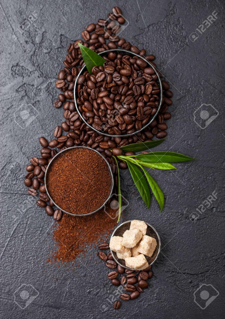 Fresh raw organic coffee beans with ground powder and cane sugar cubes with coffee trea leaf on black. - 127868872