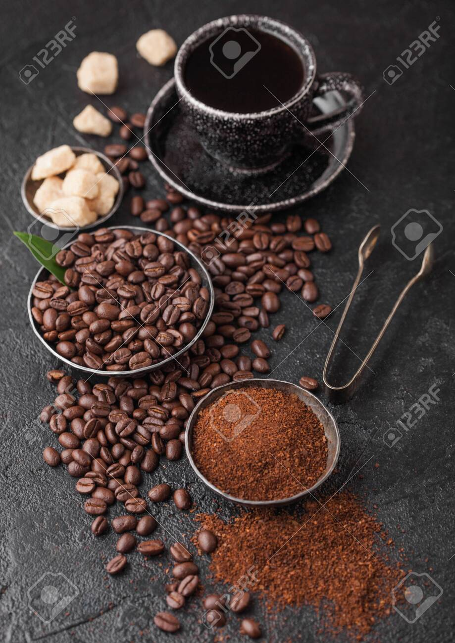 Cup of fresh raw organic coffee with beans and ground powder with cane sugar cubes with coffee tree leaf on dark background. - 138192535