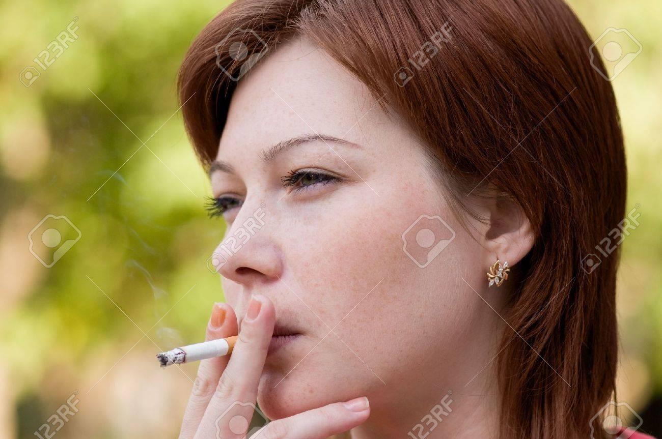 若い女性はタバコを吸う空気中の...
