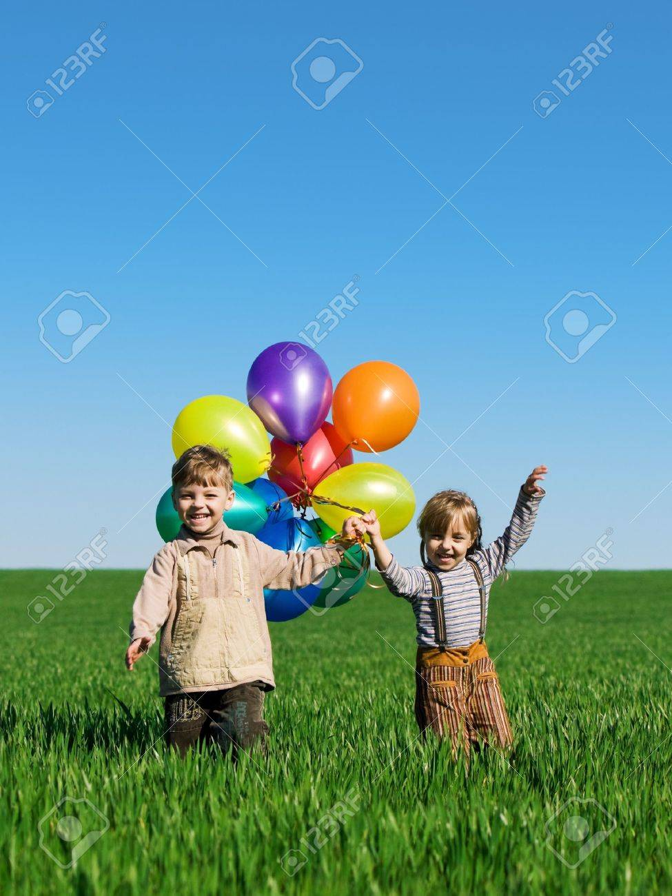 Happy sister and brother with balloons walking on the spring field Stock Photo - 7157107