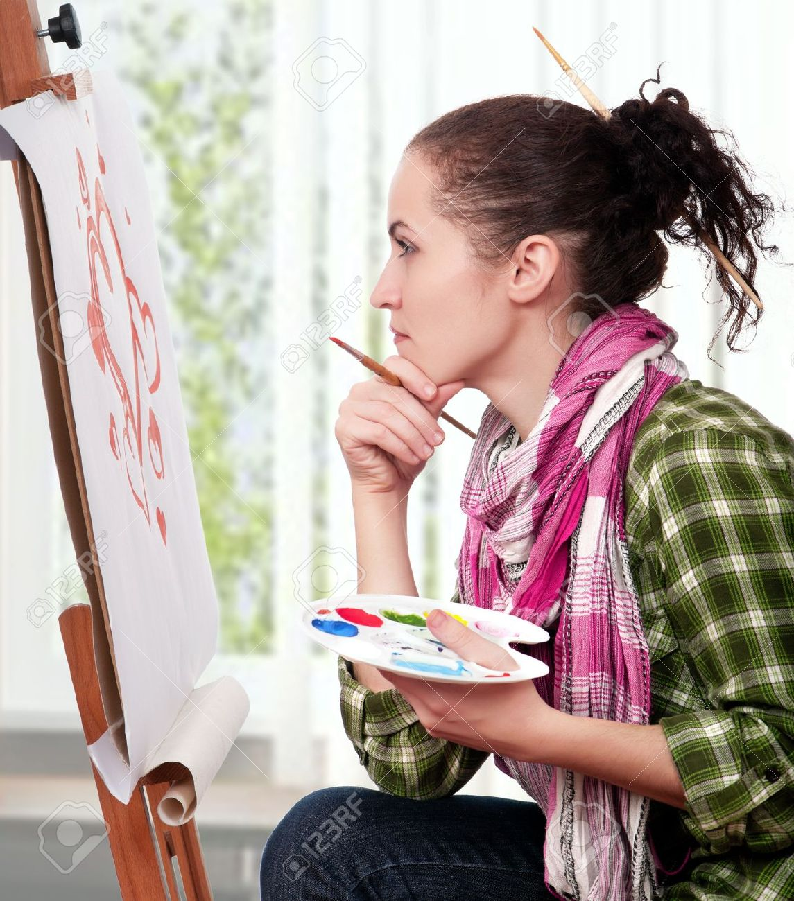 Beautiful girl with brushes near easel, painting on canvas. Stock Photo - 8380860