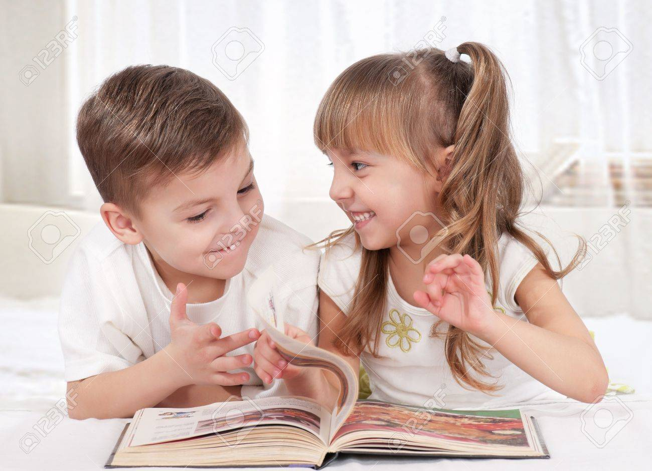 Lovely children - brother and sister, reading a book, on the bed Stock Photo - 9104254