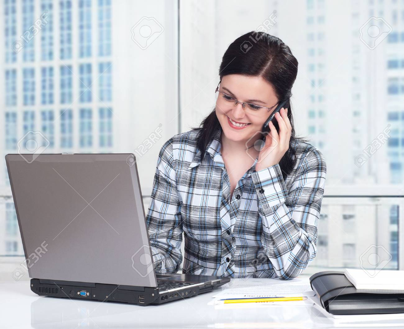 Portrait of a pretty young woman with phone in front of a laptop computer Stock Photo - 9271484