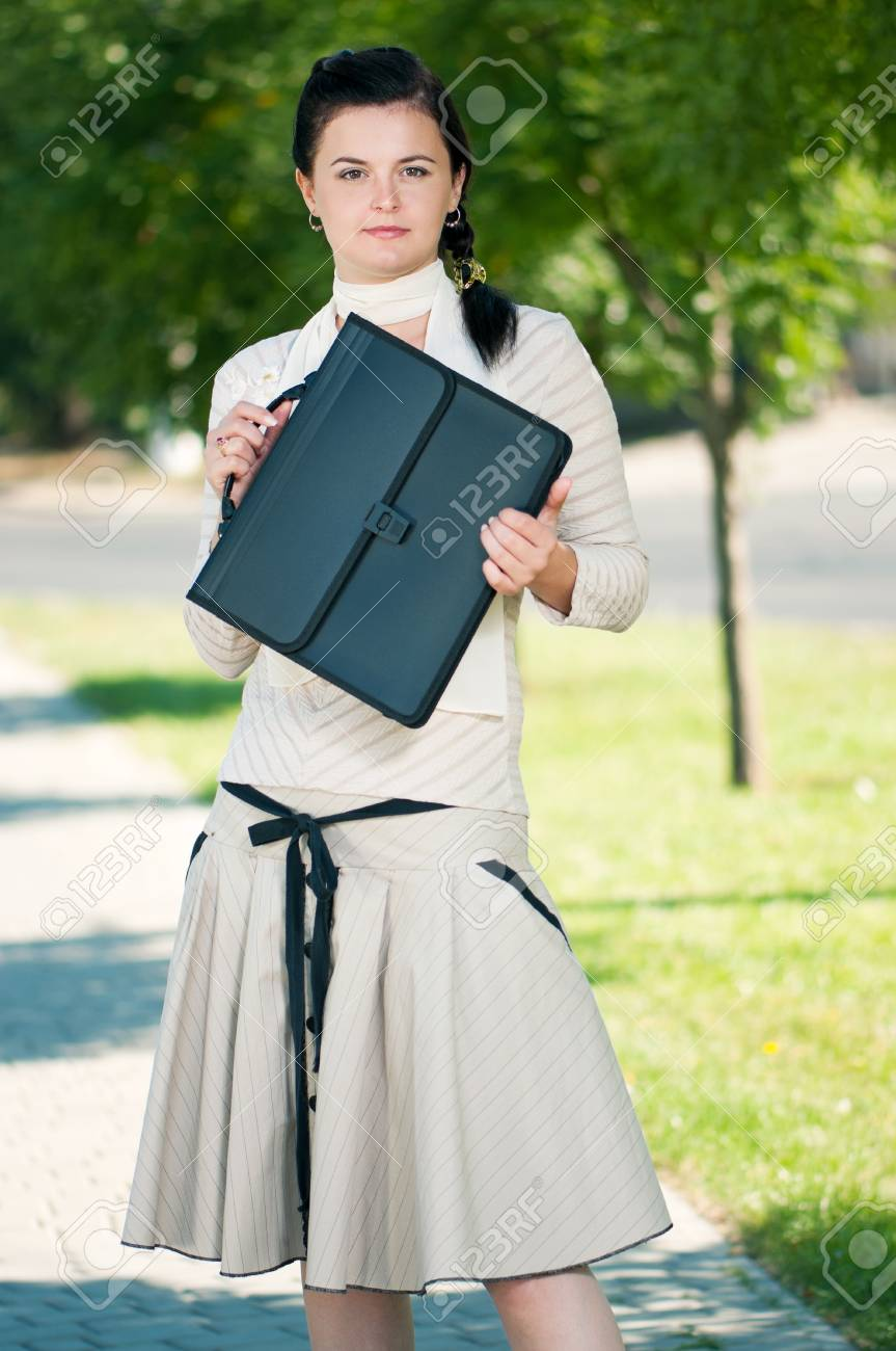 Modern young business woman with briefcase in park outdoors Stock Photo - 12075491