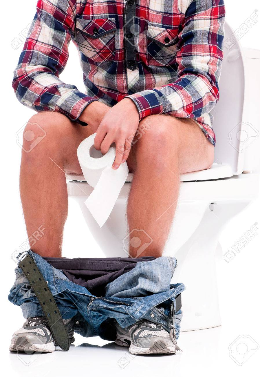 Man is sitting on the toilet bowl, holding paper in hands, on white background Stock Photo - 27103330
