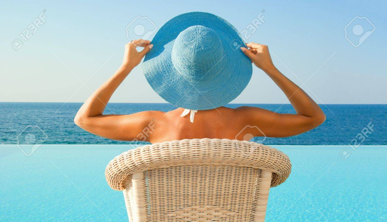 Attractive woman in hat relax near edge of infinity pool and looking to horizon in sunny day Stock Photo - 14903233