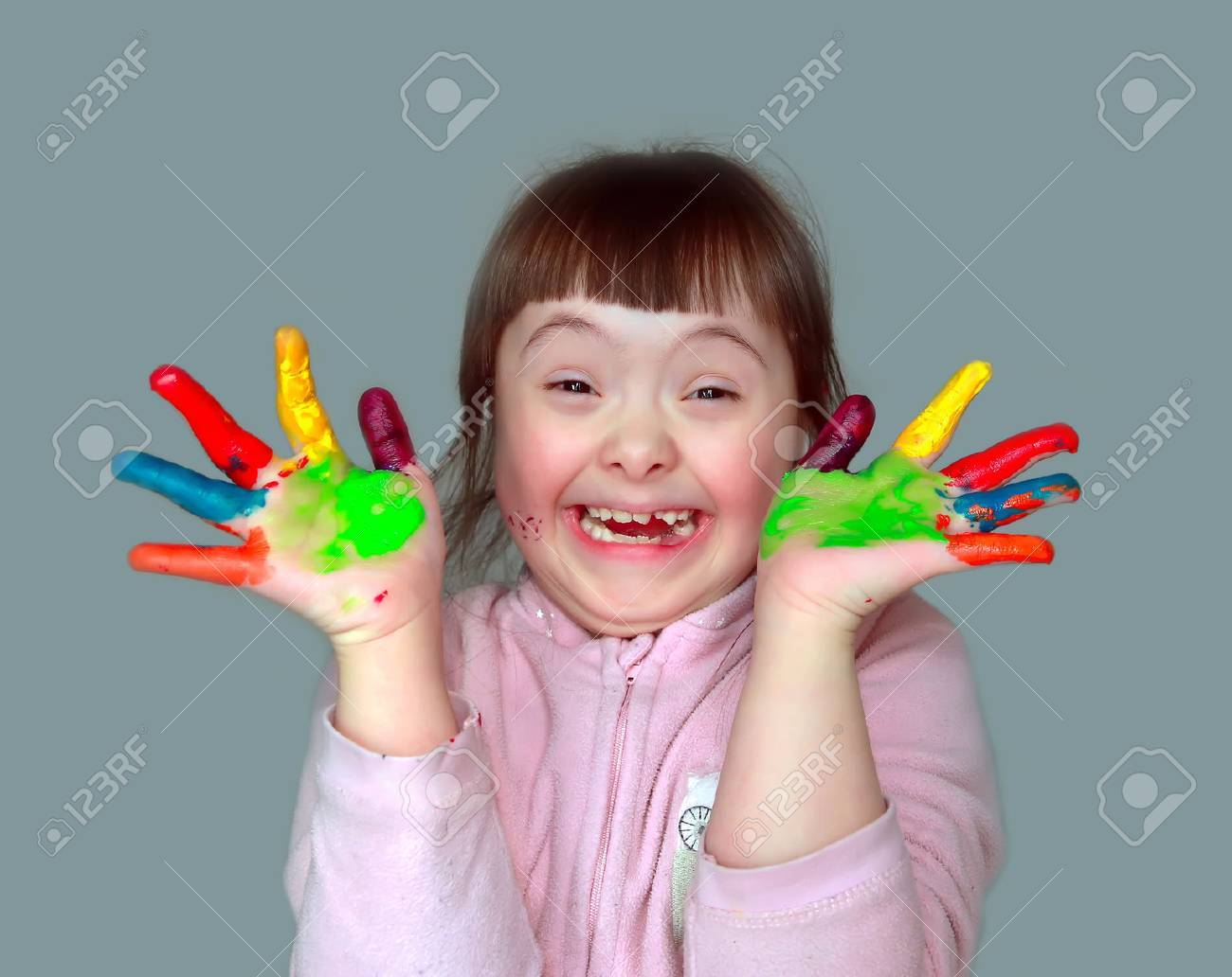 Cute little girl with painted hands. Isolated on grey background. Standard-Bild - 36953609