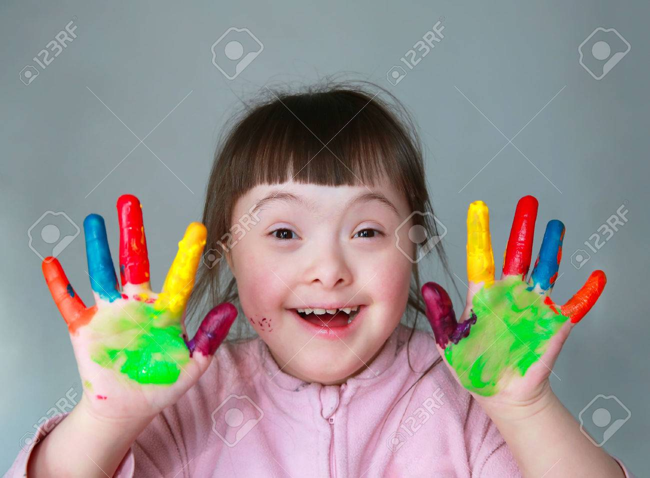 Cute little girl with painted hands. Isolated on grey background. Standard-Bild - 37086854