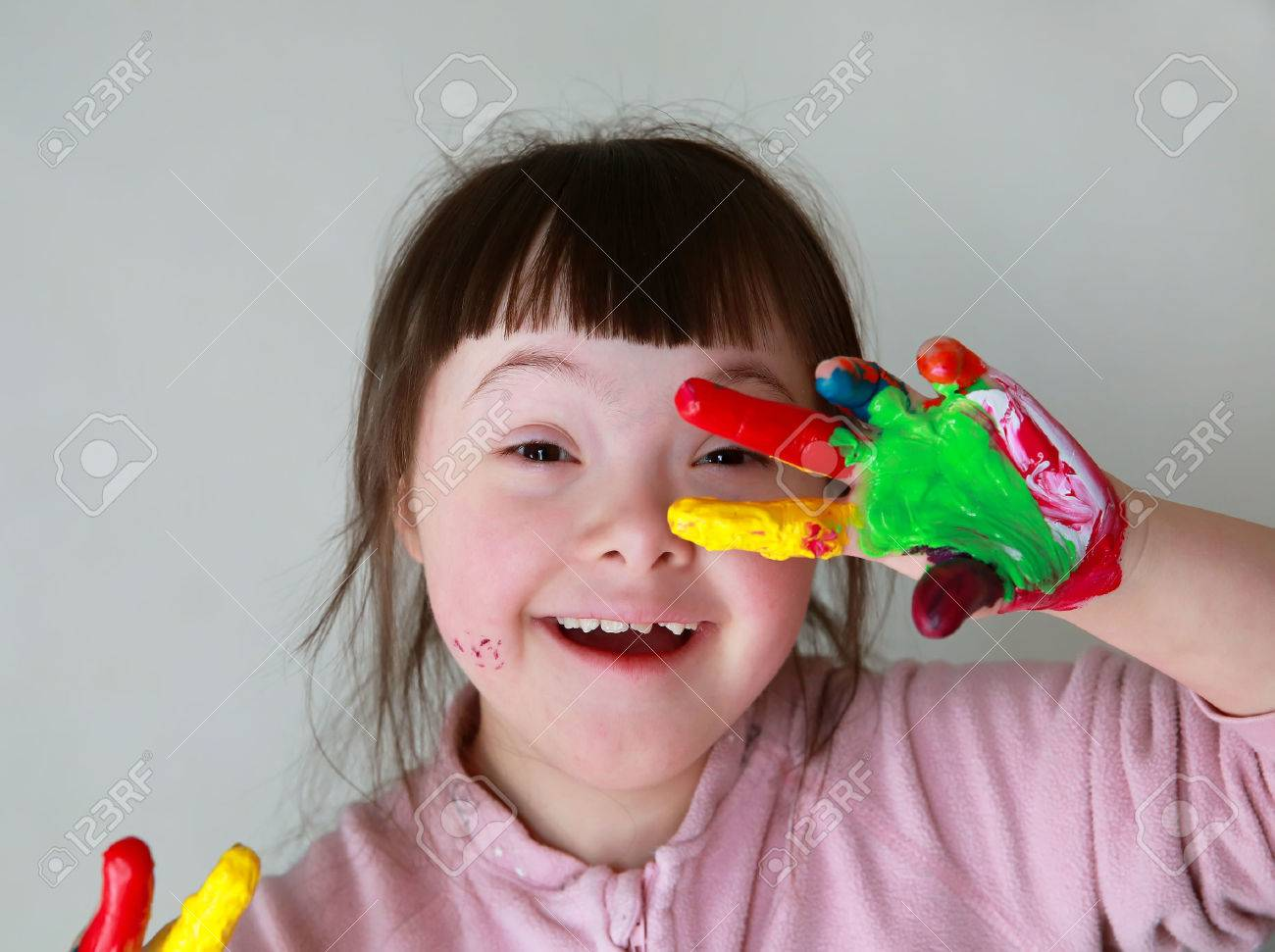 Cute little girl with painted hands. Isolated on grey background. Standard-Bild - 37612722