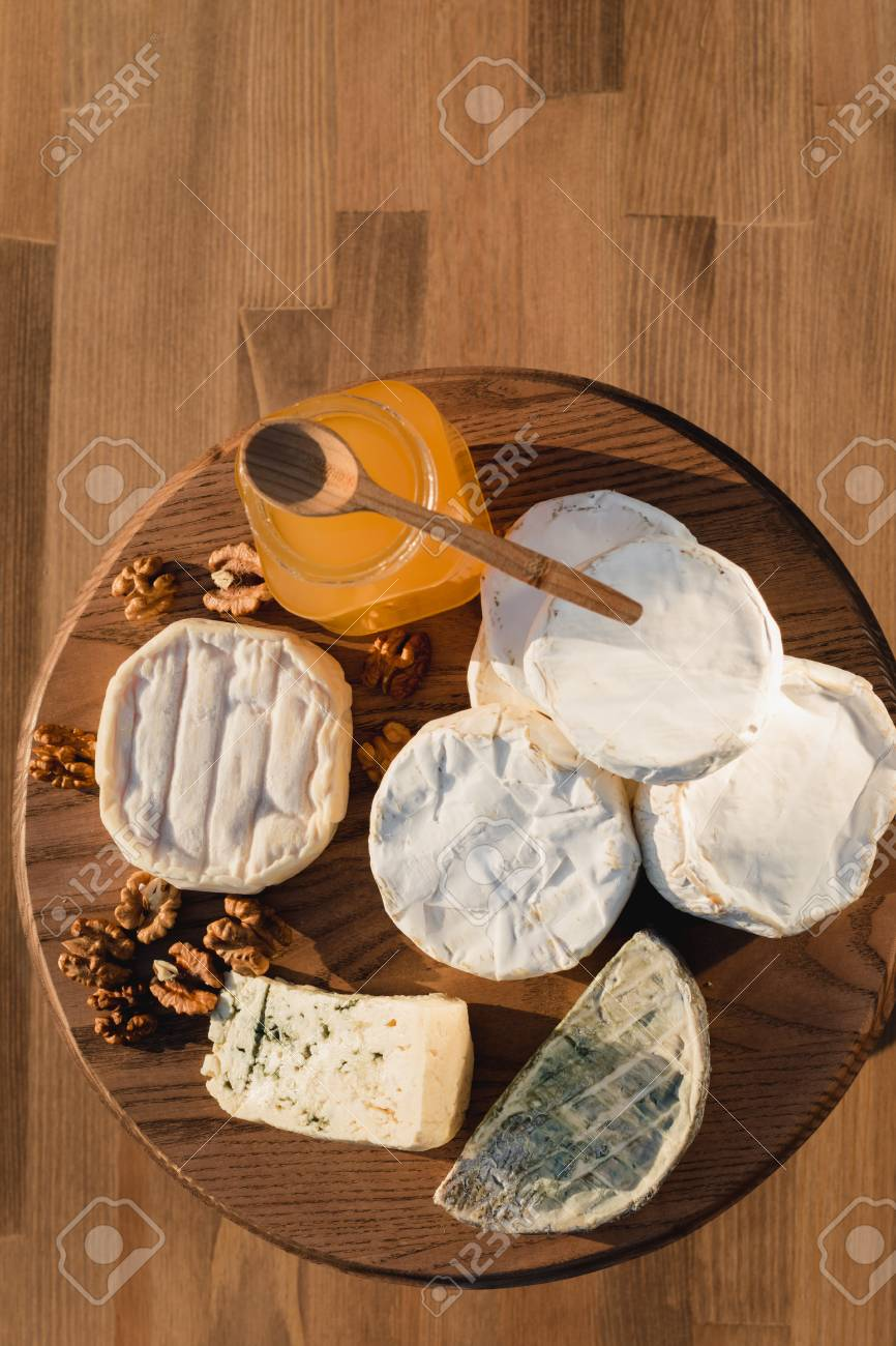 cheese plate. different cheeses on a wooden plate. cheeses of honey and nuts. & Cheese Plate. Different Cheeses On A Wooden Plate. Cheeses Of ...
