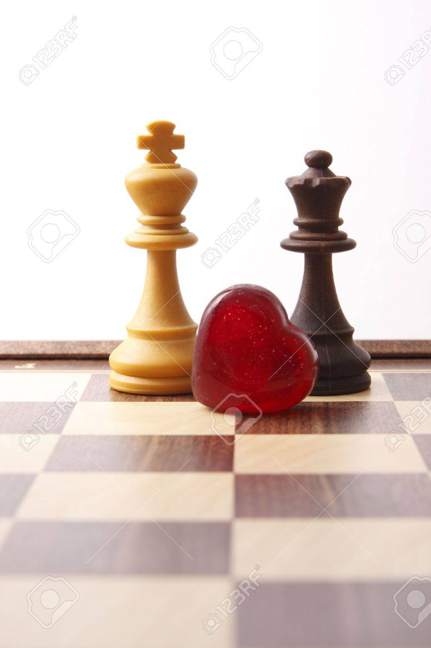 Stock photo white king and black queen on chessboard with heart