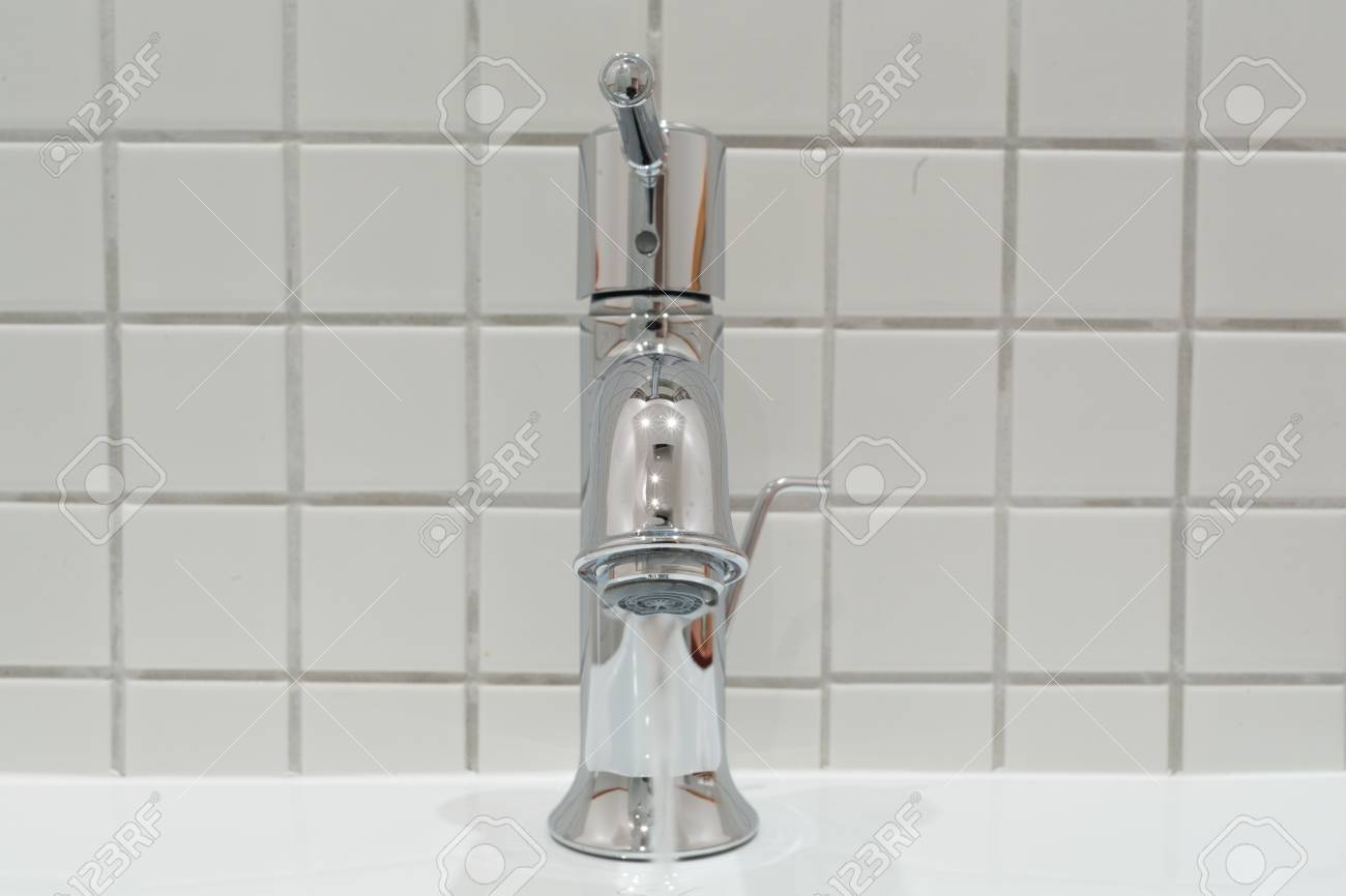 Water Flowing Out Of A Silver Faucet In A Bathroom Handbasin Stock ...