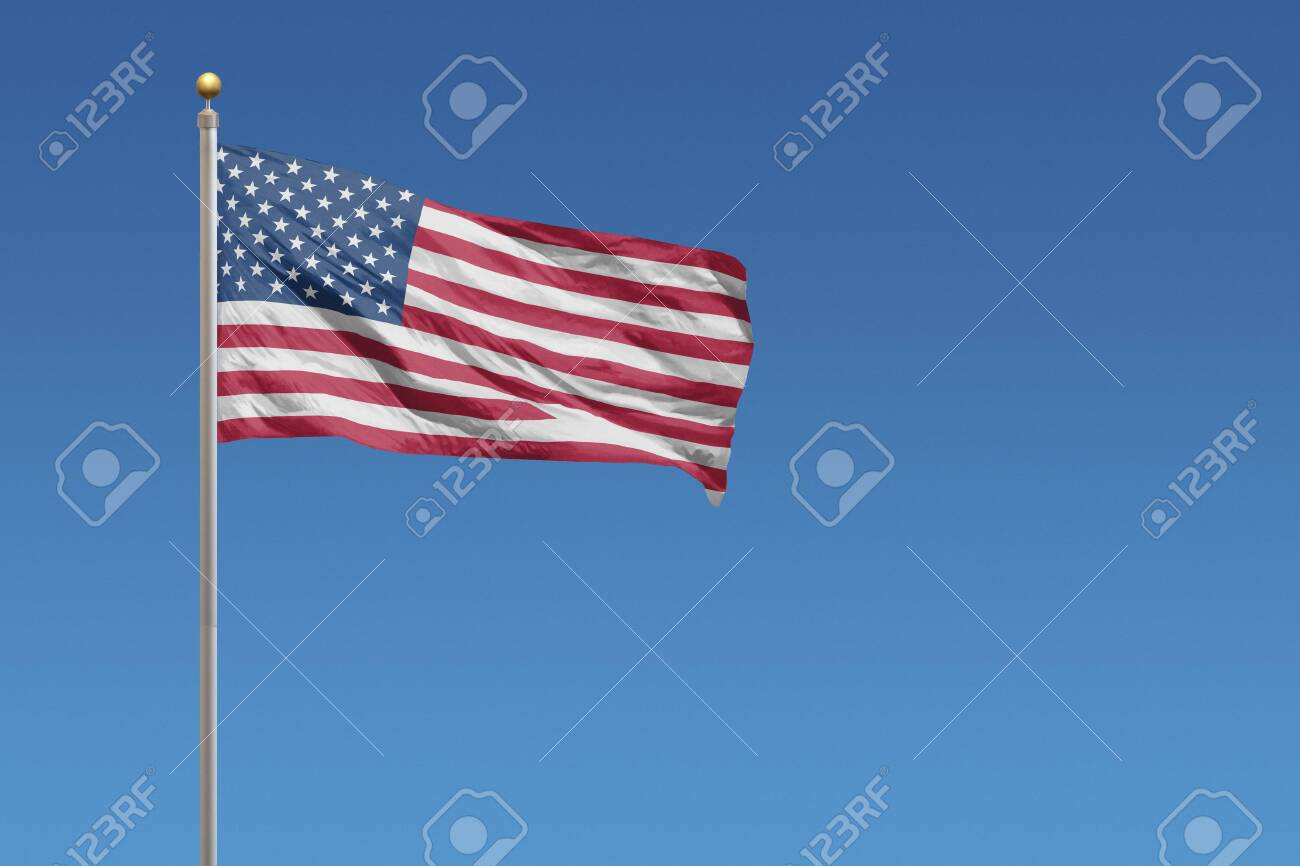 Flag of United States in front of a clear blue sky - 132353696