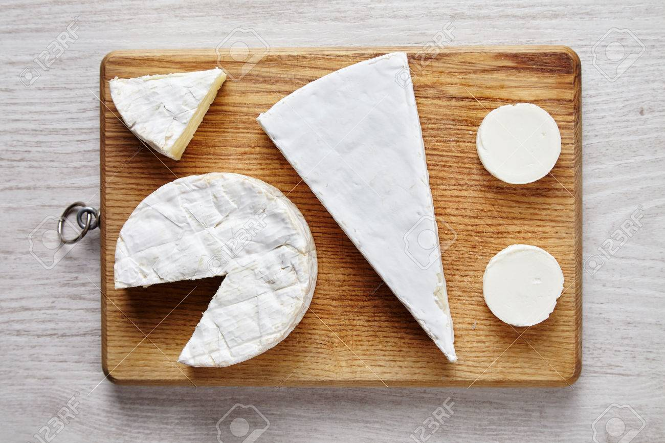 Avangard white soft cheeses: goat, brie, camembert on wooden desk on white table top view - 48538331