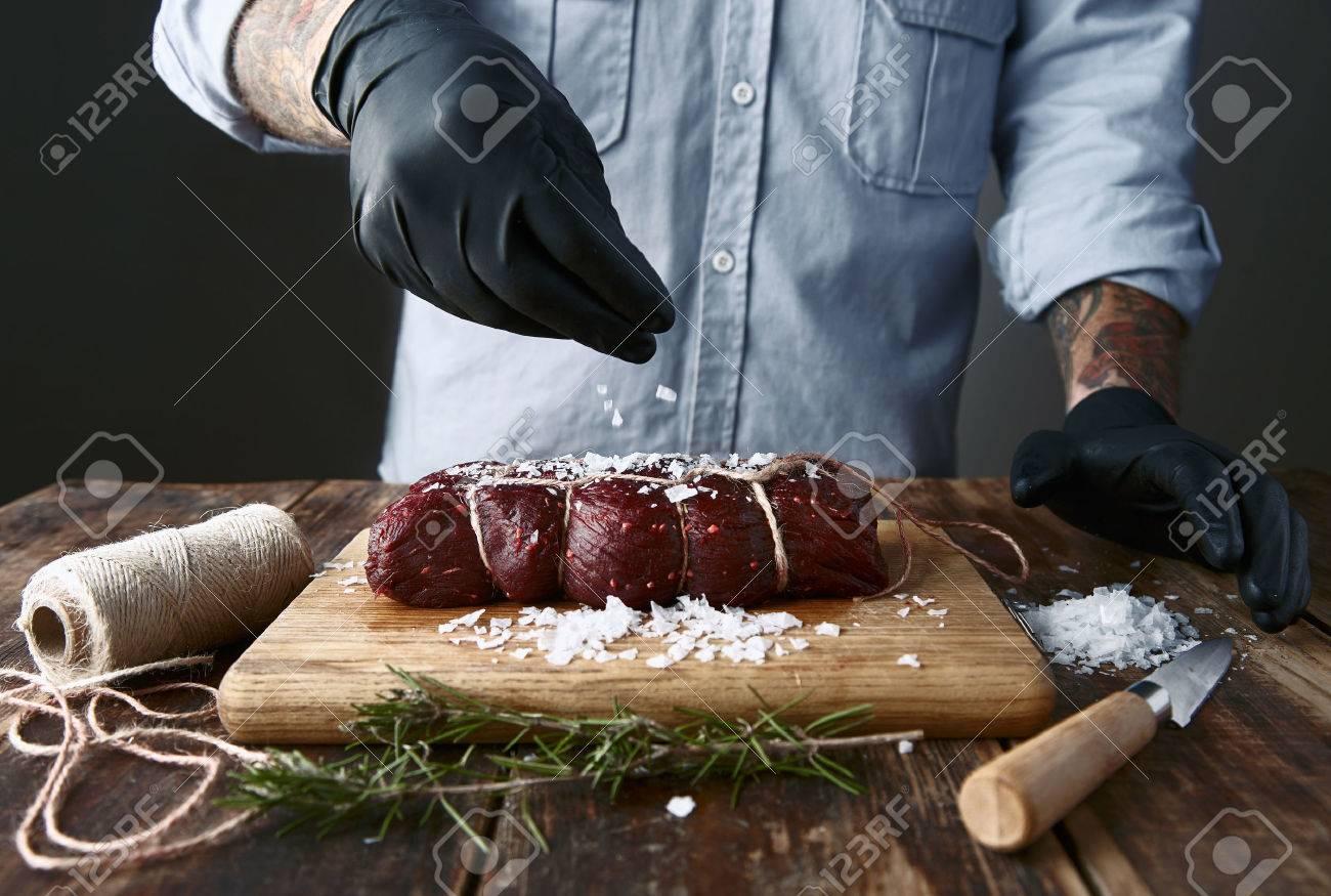 Tattoed butcher in black gloves salts tied piece of meat to smoke it. - 48953970