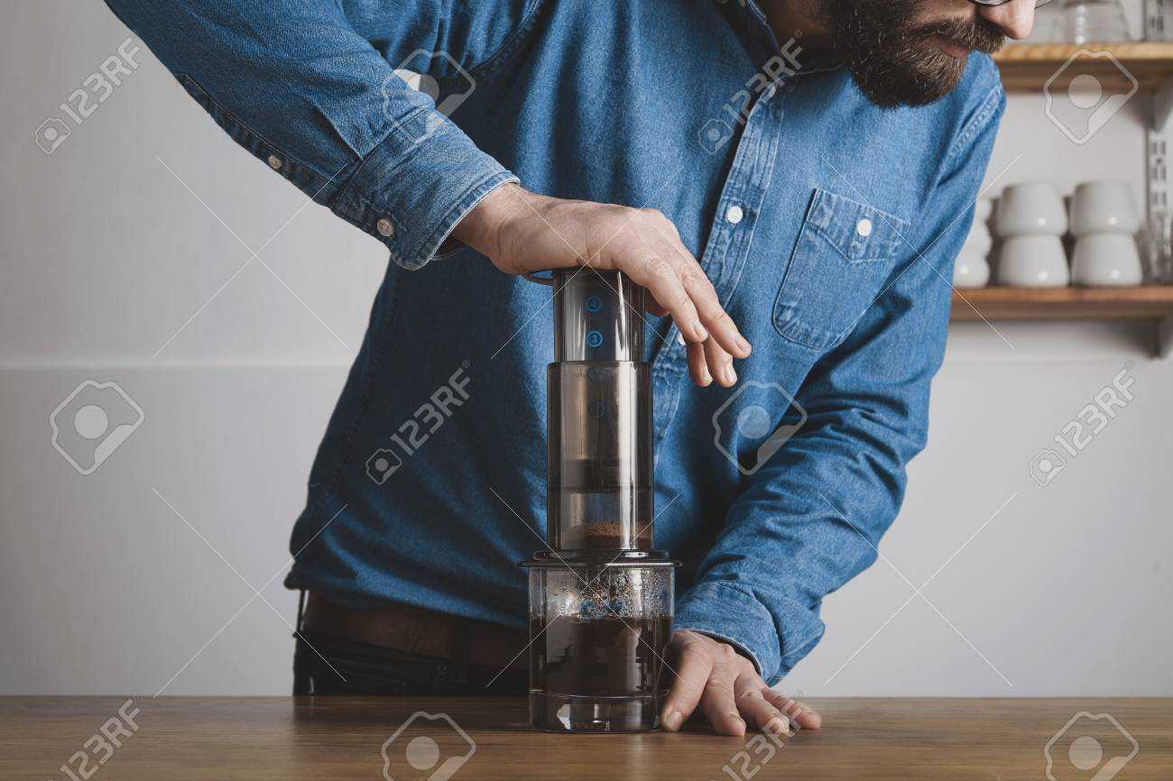 Step by step aero press coffee preparationBearded barista in blue jeans shirt press aeropress to fill glass with beverageProfessional coffee brewing cafe shop - 52789021