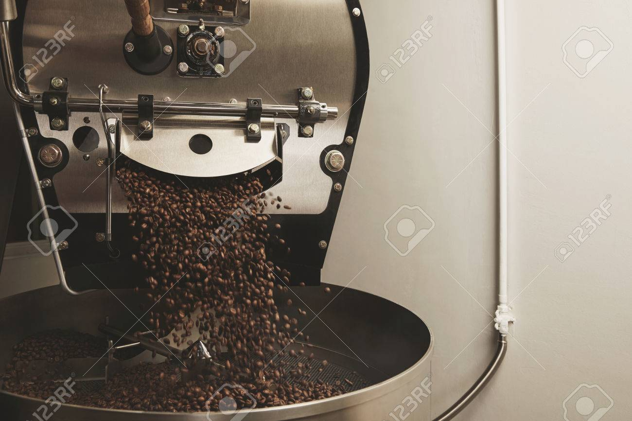 Hot freshly baked coffee beans fall from best professional large coffee roaster being poured into the cooling cylinder with motion blur on the beans Side centered - 53354372