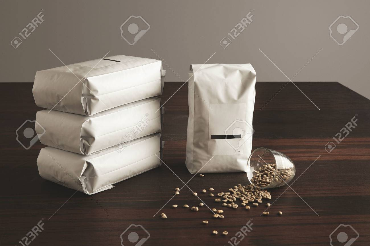 Big hermetic package with blank label presented near other four lying pouches filled with roasted coffee, near fallen transparent glass with raw sampled coffee beans spreaded on red table - 56928730