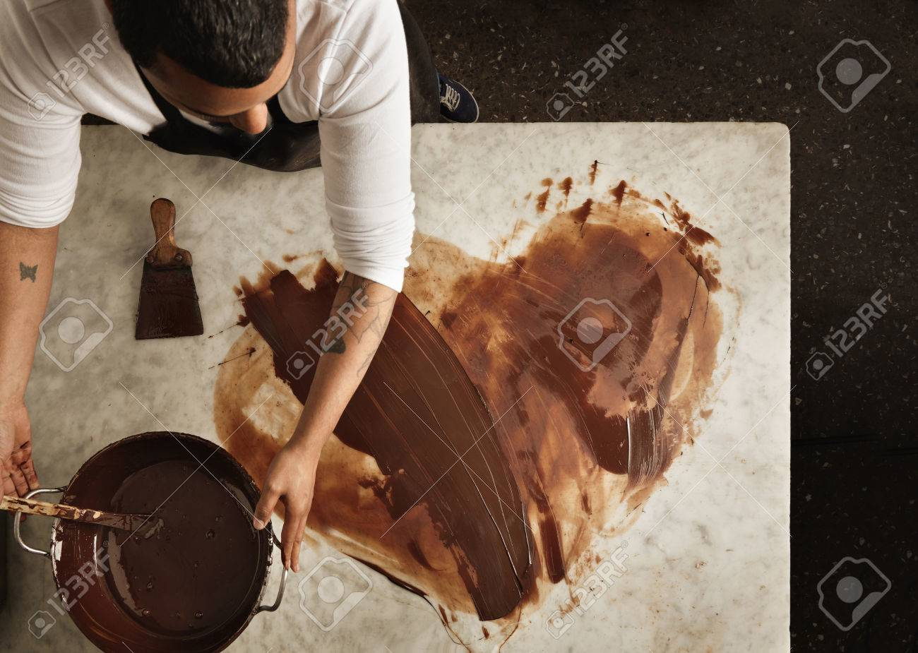 Top view professional black baker uses hot chocolate to draw a lovely heart, before makint sweet organic bars as romantic gifts for valentine day. Isolated on marble table in artisan retro laboratory - 56928754