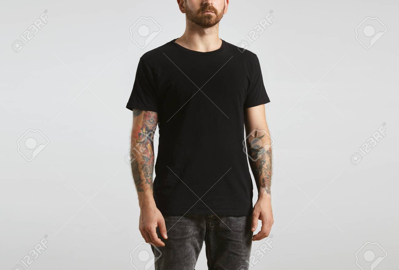 Brutal attractive bearded biker man with tattooed hands poses in black blank t-shirt from premium thin cotton, isolated on white mockup - 59348621