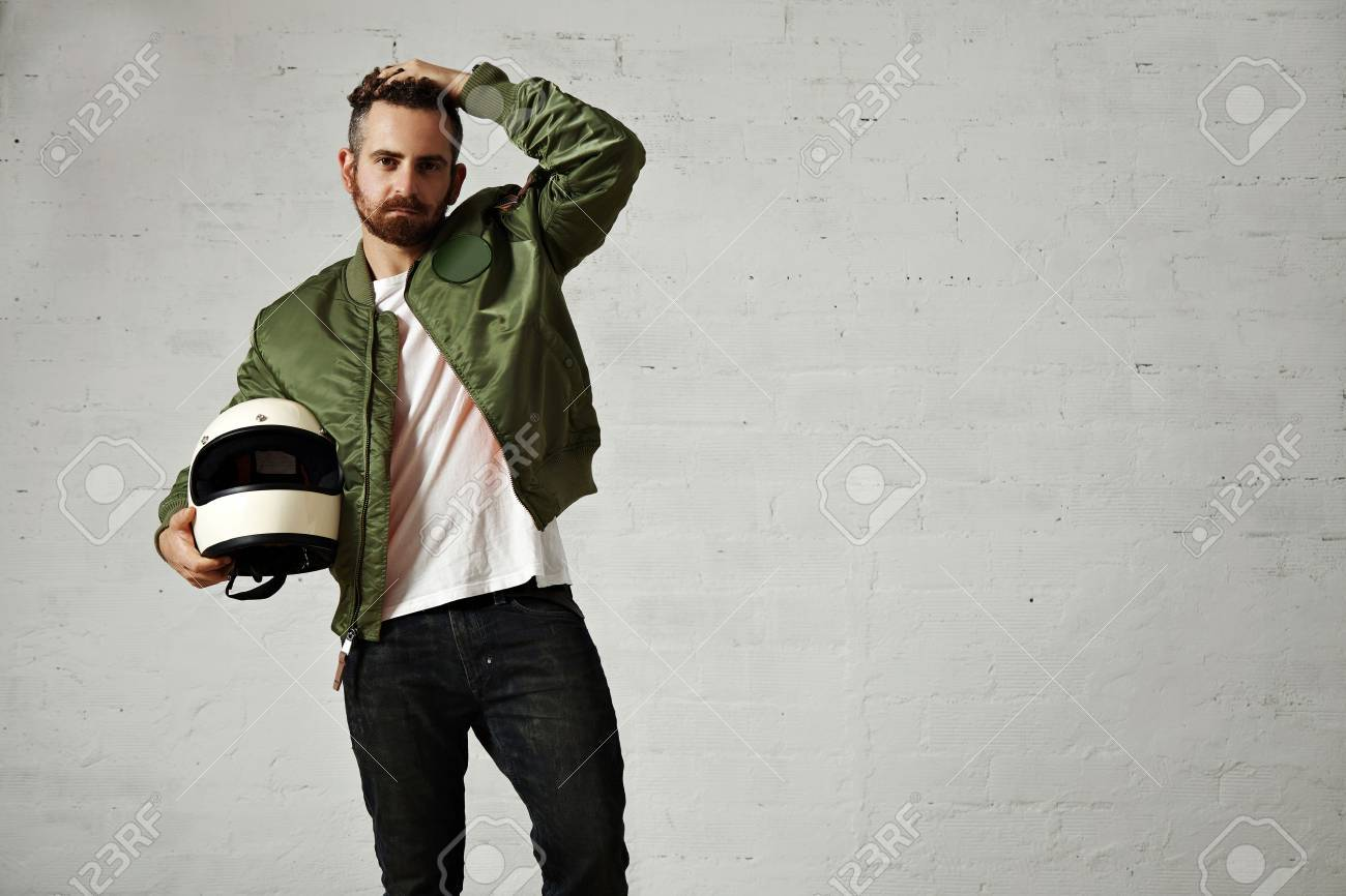 Tired young motorbiker in green bomber jacket, black jeans and white t-shirt adjusting his hairstyle and holding his white helmet - 65865315