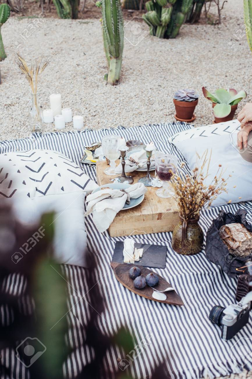Still life of romantic picnic setup in park, for surprise birthday party, date or engagement location, candles and exquisite luxurious snacks to create atmosphere of chic - 86878048