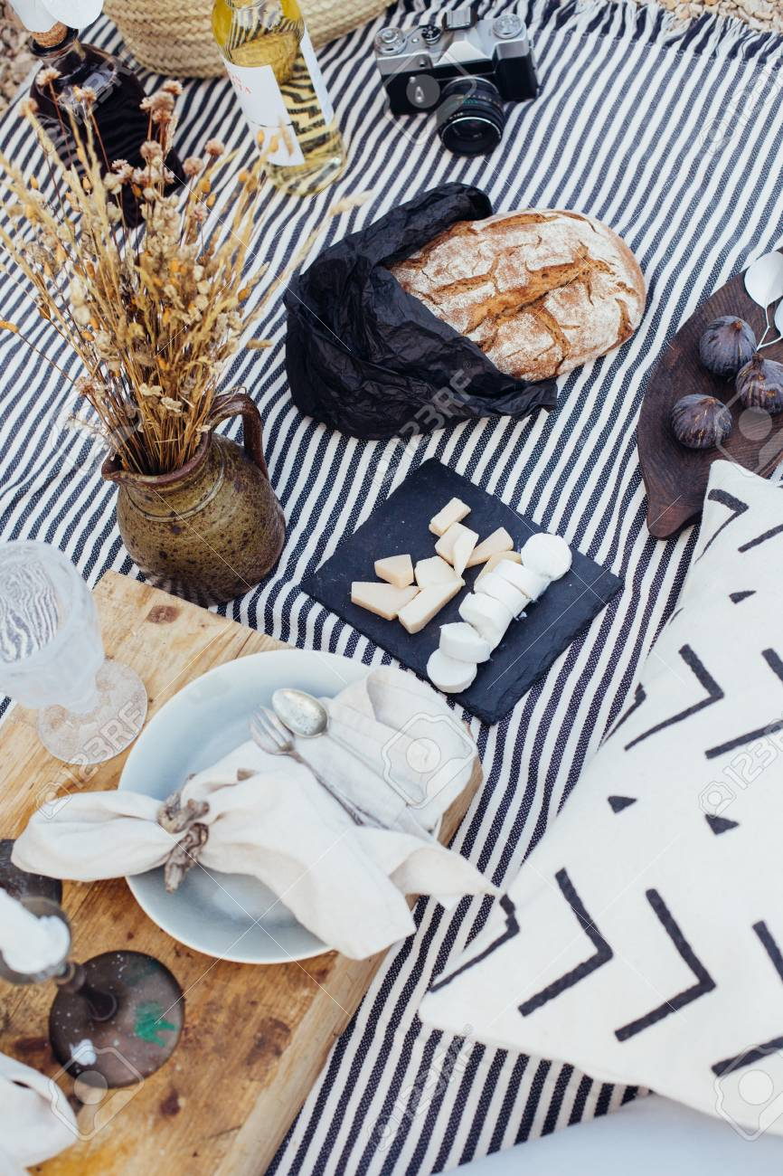 Natural fresh and organic products, cheese, wine, bread and figs arranged for romantic getaway for couple, on picnis blanket with pillows and candles and vintage decoration - 86878050