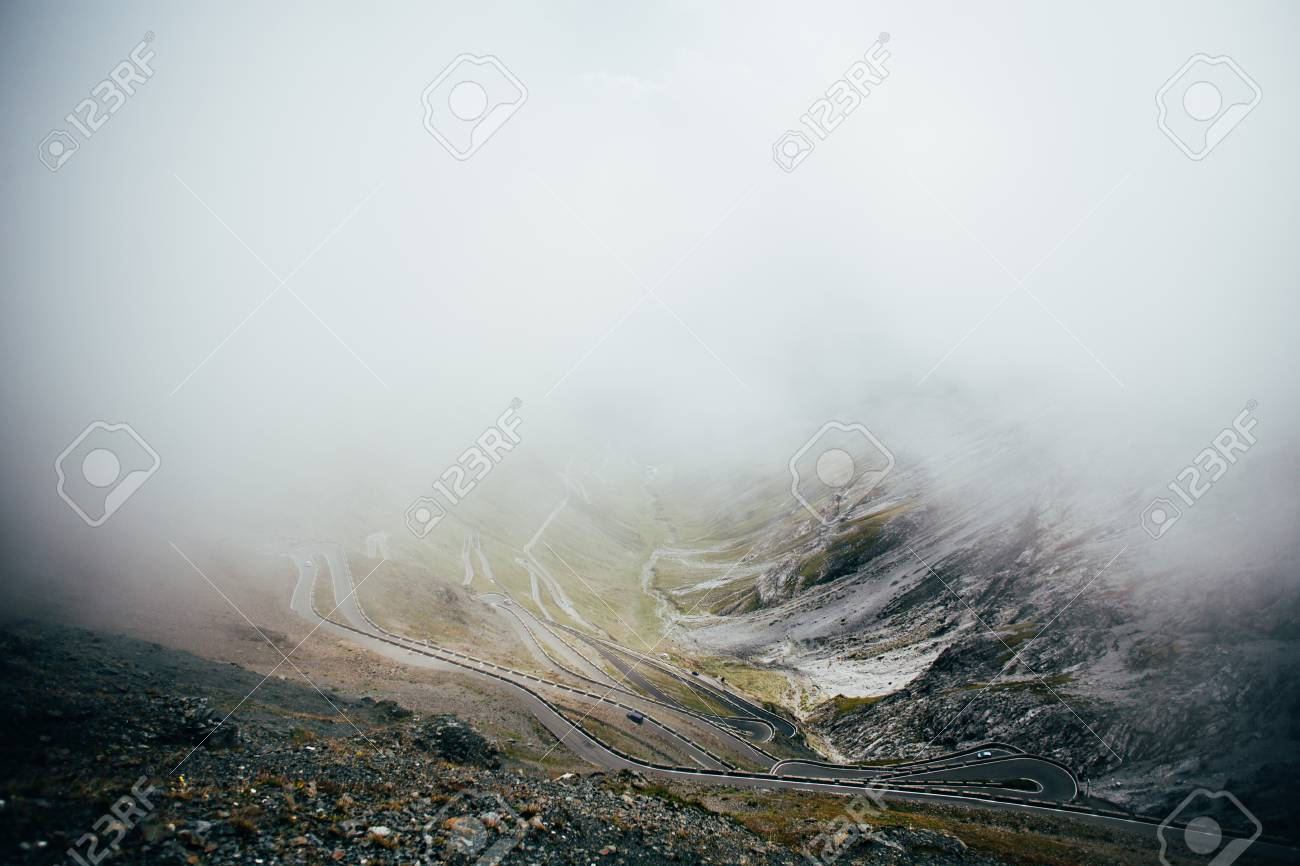Winding road with switchbacks and hairpin turns climbing up side of mountain of stelvio pass in italian dolomites lost in clouds or fog, concept travel, adventure - 86878052