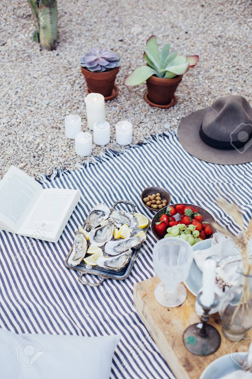 Still life of romantic chic setup for picnic blanket table with candles, flower decoration, fruits and strawberries in bowl, novel book and fresh seafood oysters - 86878053