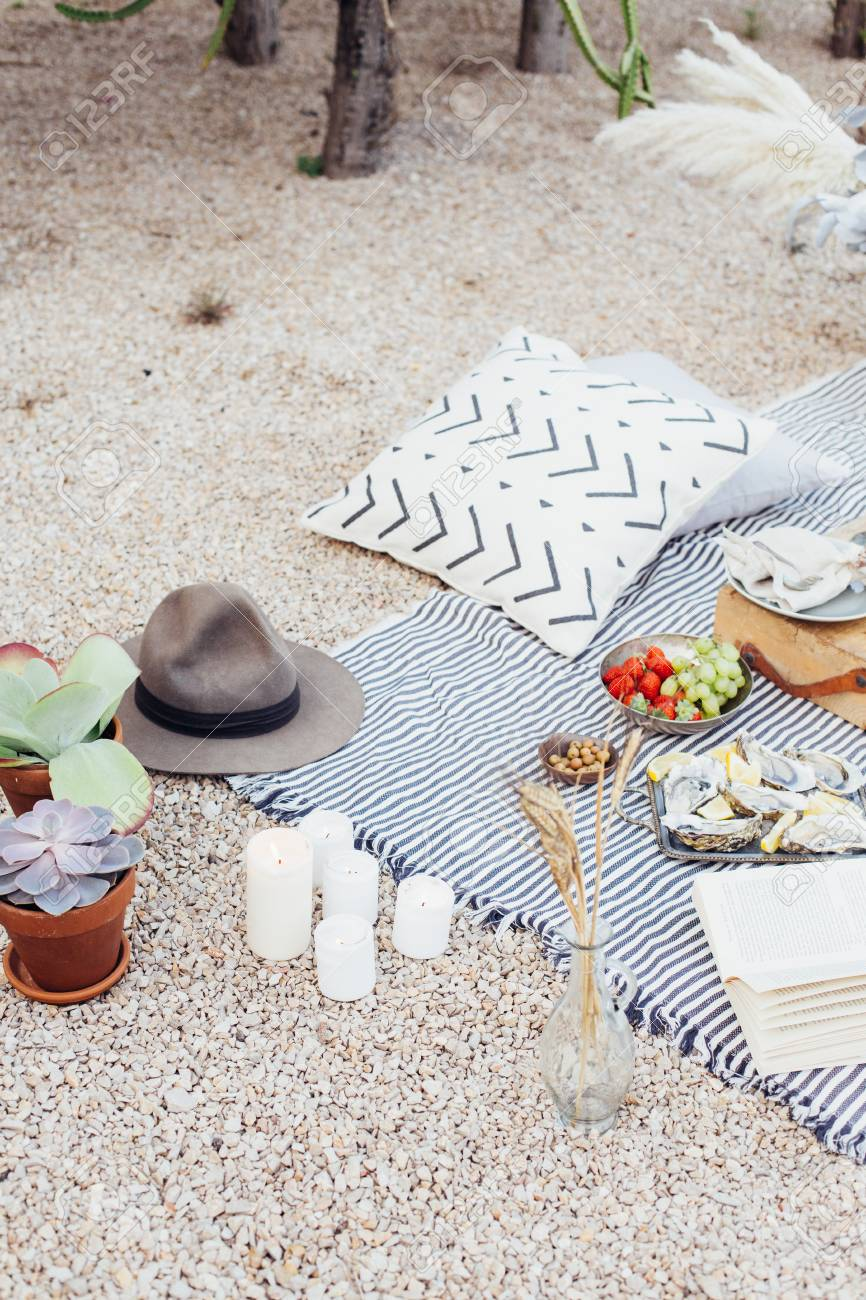 Top view on still life outdoor picnic blanket setup for romantic day or night out for hipster stylish couple, wedding, proposal happening with candles and chic snacks - 86878057