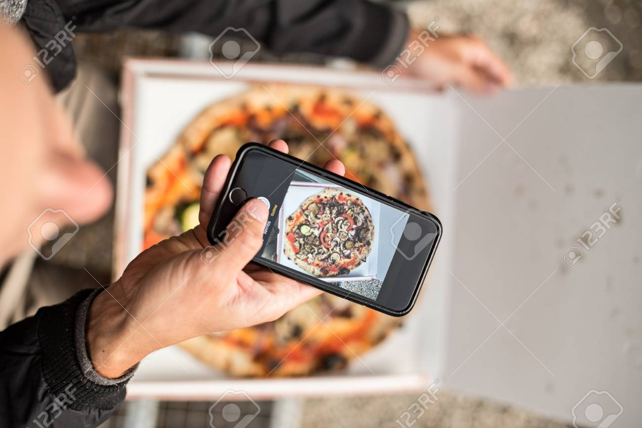 Social media influencer millennial hipster taking photo of his fresh pizza - 86878060