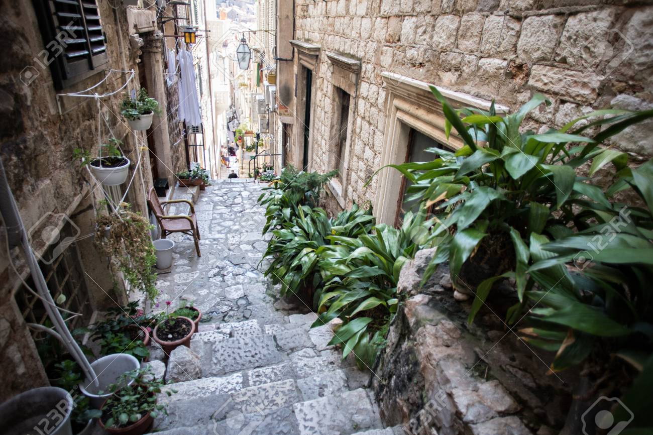 Beautiful narrow street going down, paved with cobbles and decorated with green plants benches and chairs, Dubrovnik Croatia - 86878063