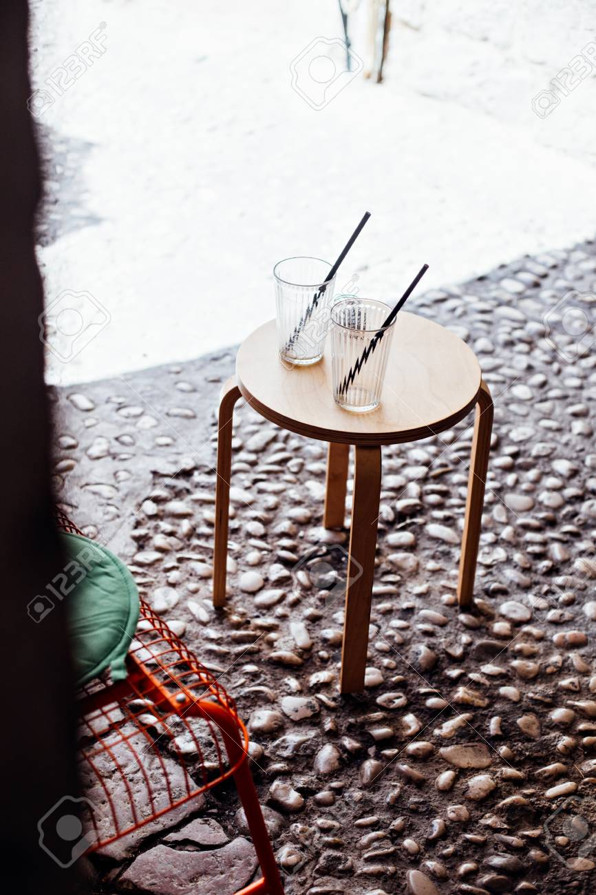 Two empty glasses or jars of coffee, juice or lemonade with straws stand symmetrically on wooden table in front of cafe or bar in old town of dubrovnik - 86878064