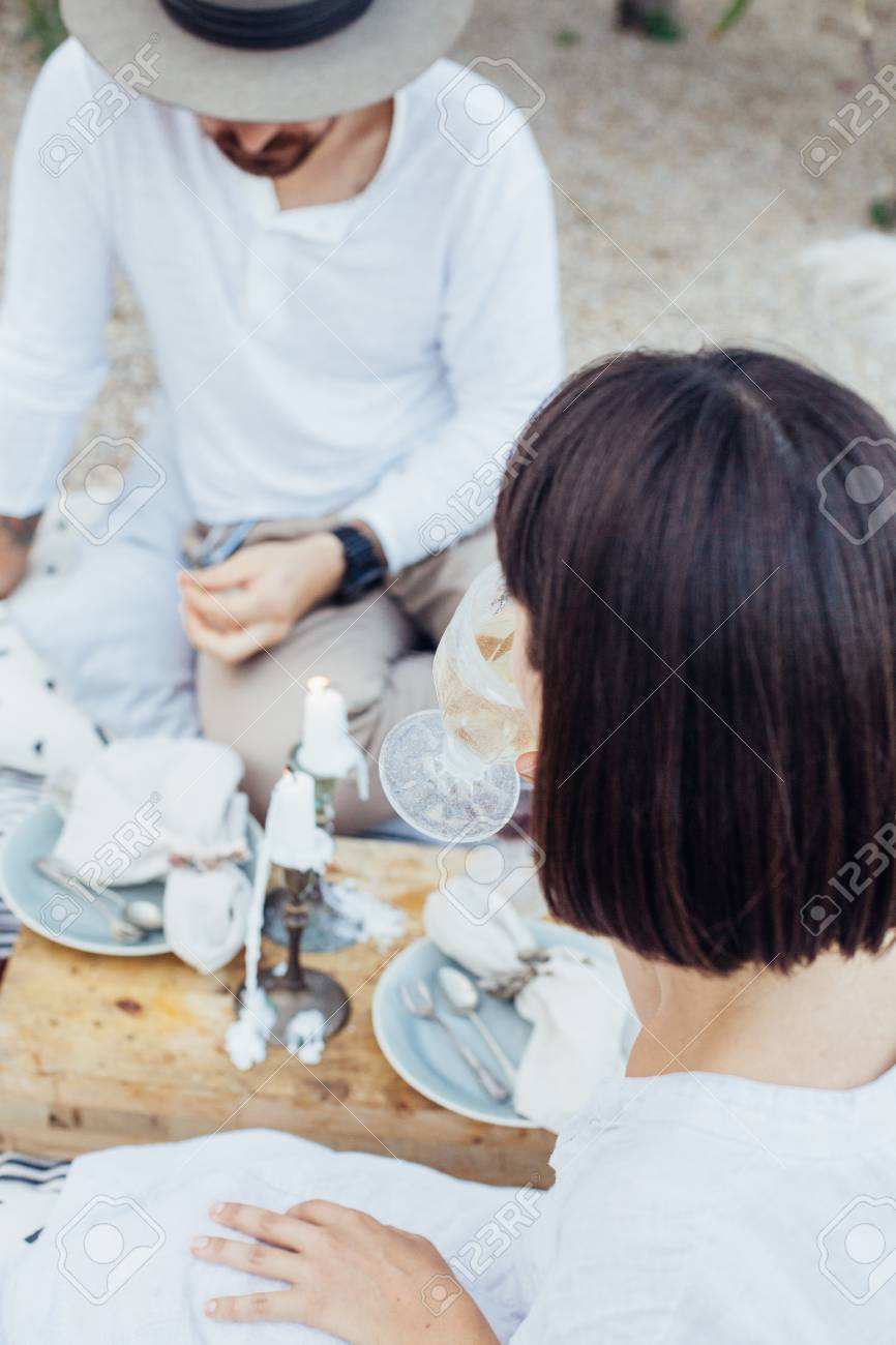 Soft focus shot of beautiful hipster couple on chic romantic date or wedding or engagement proposal, they drink wine, laugh and flirt, eat snacks and fruits - 86971706
