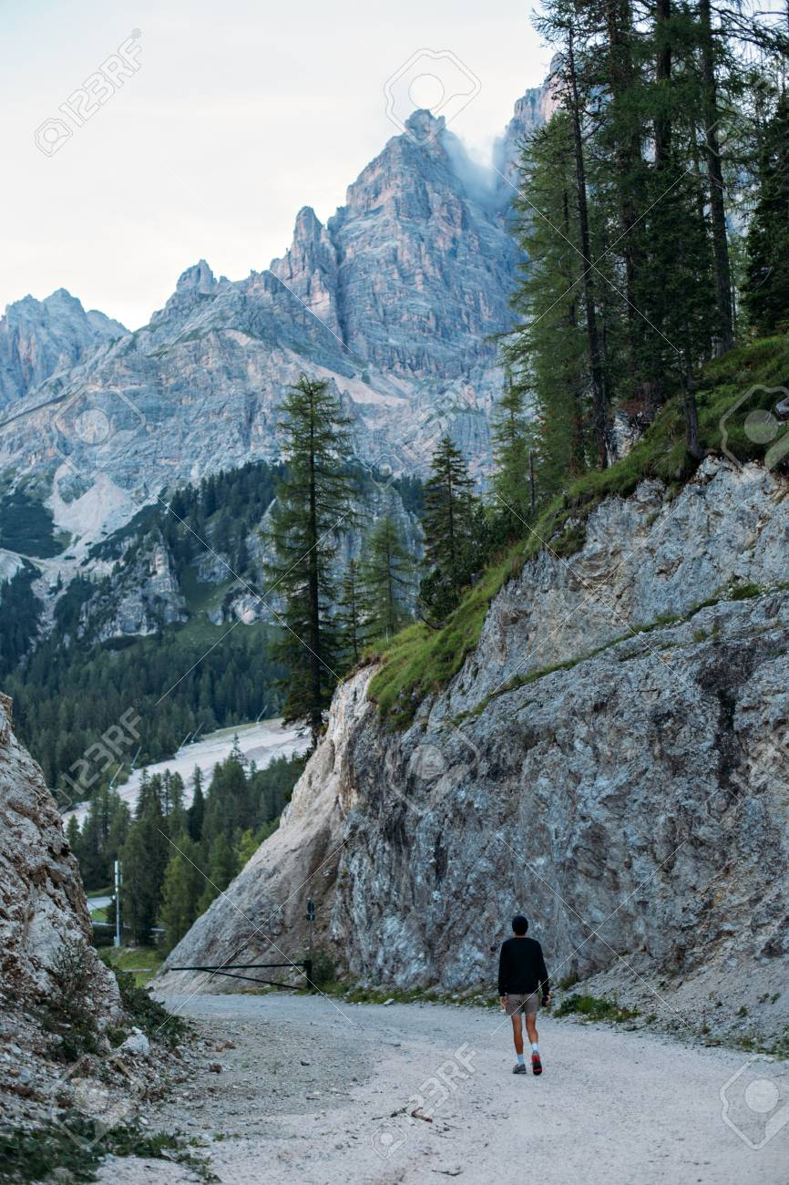 Curious explorer male figure of adventurer nomad traveler walks on path inbetween mountains and forest high in italian dolomites - 86878066