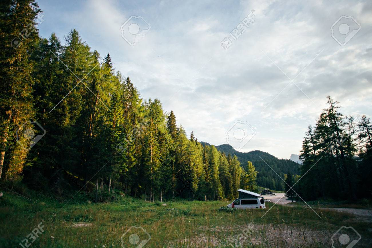Empty wild camping site lost in green forest on early morning or sunset, with white travel van camped out with folding roof, concept nomad life off grid, adventures - 86878070