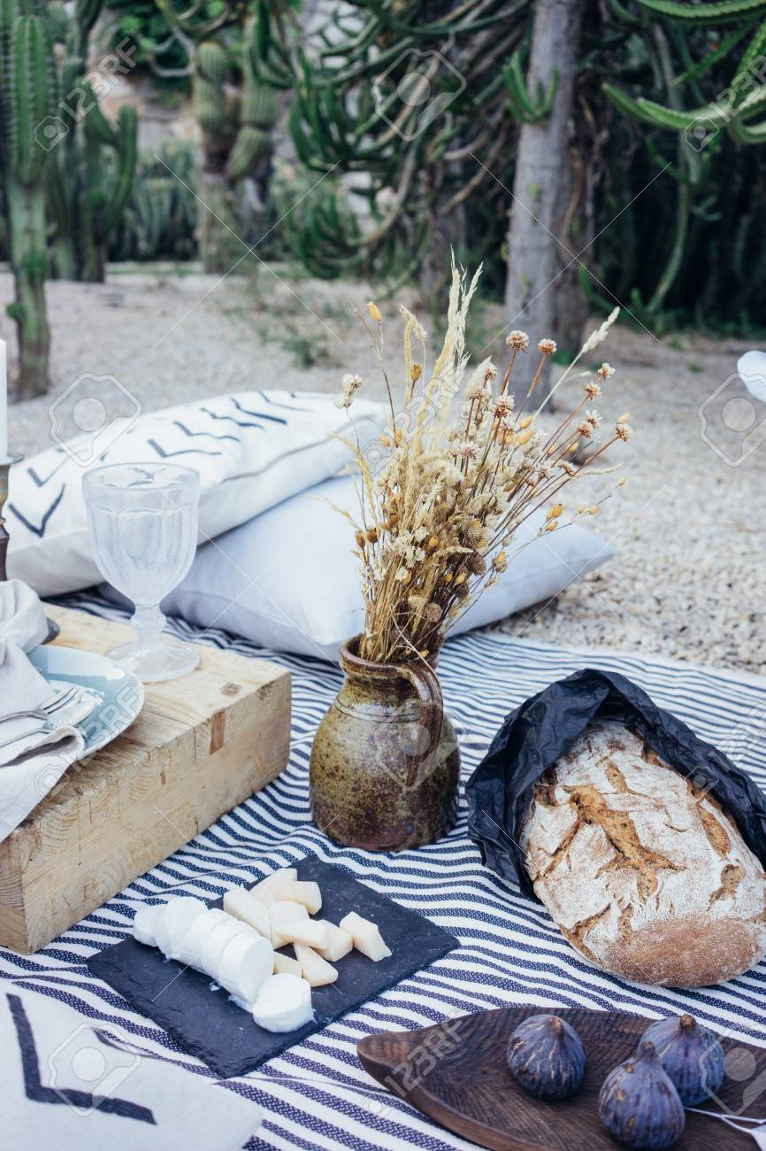 Beautiful arranged table in park for date or dinner or picnic, with jar of flowers, cheese set variety, figs, artisan home made bread, ideal setup for rustic wedding - 86878075