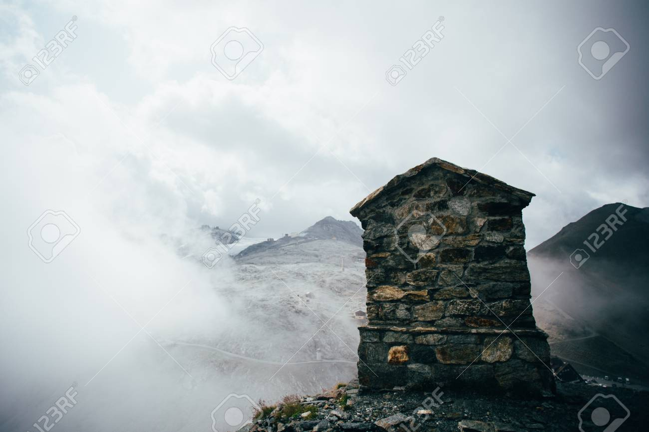 Structure made of stone and bricks to commemorate or signal top of summit on mountain covered with clouds, alps or dolomites, exploration and hiking guide - 86878076