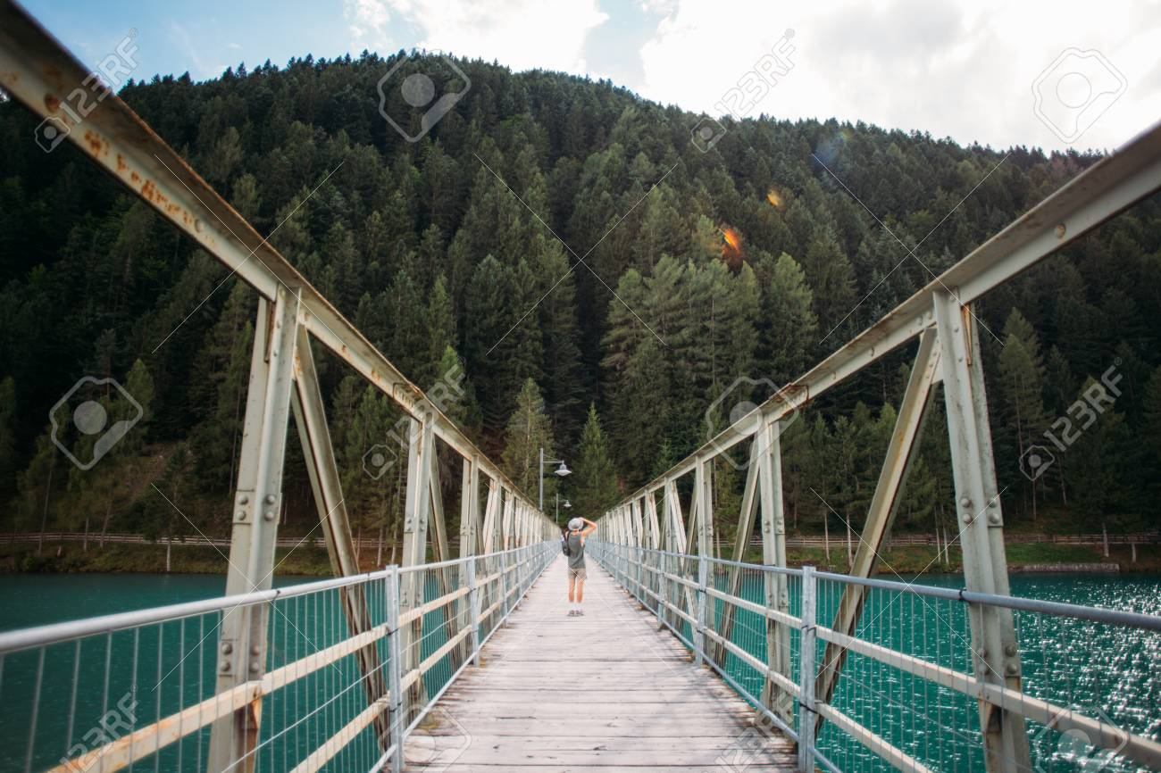 Young fit adventurer man with camera makes photo of nature, stands in middle of metal pedestrian bridge over pristine blue water lake that connects two shores, forest and city - 86878079