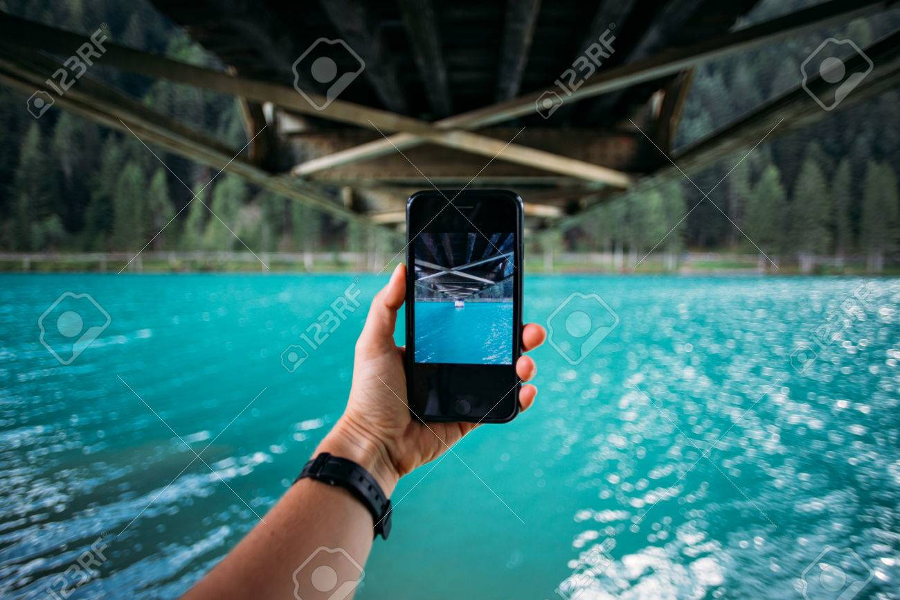 POV of hand holding smartphone and making photo of turquoise lake and bridge metal construction for share on social media channels, concept millennial nomads - 86878083