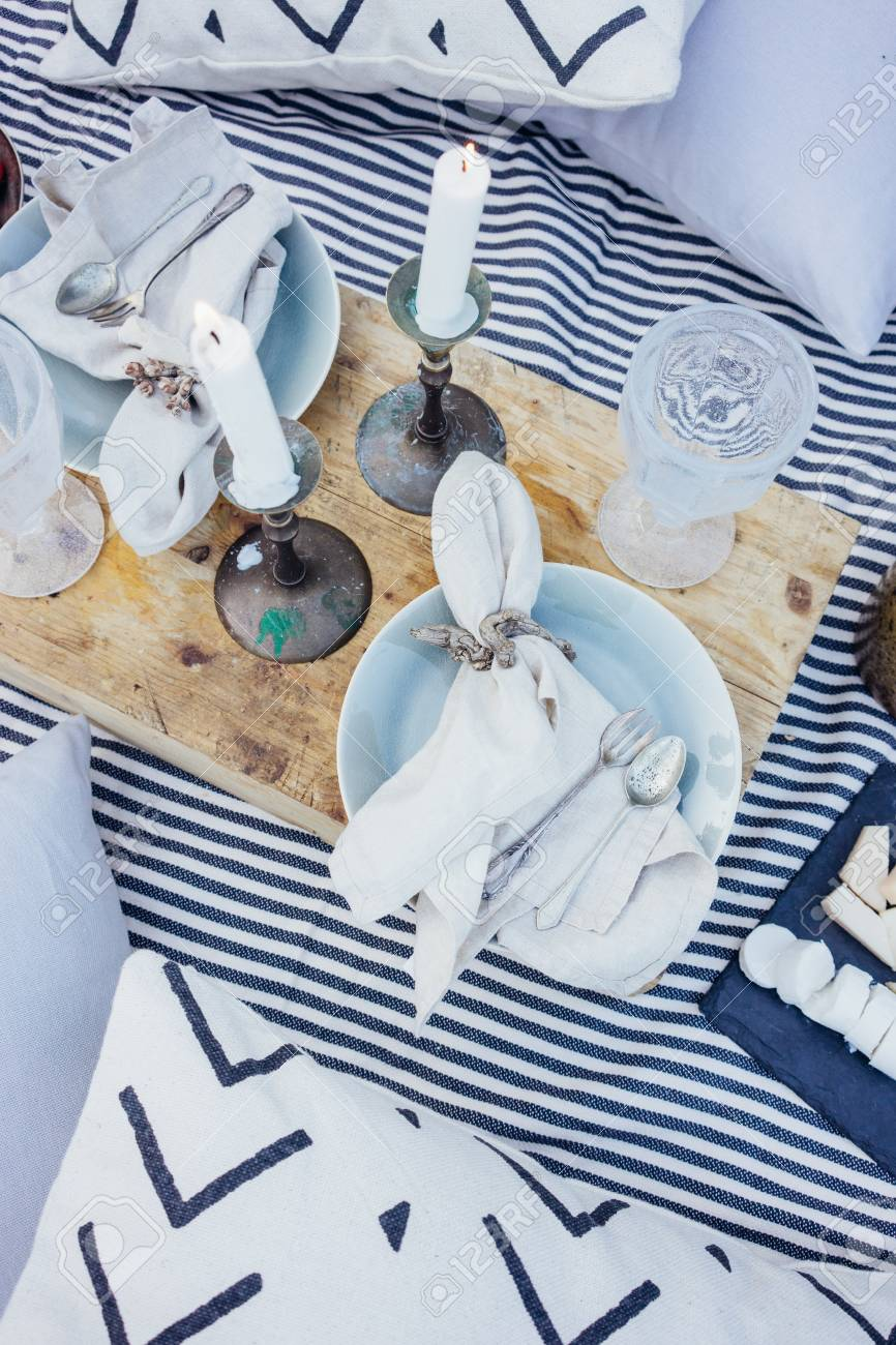 Top view on beautiful arranged table or picnic blanket, with aged antique wooden tray, pillows, candles, vintage cutlery and ceramic plates, decorated with candles - 86878085