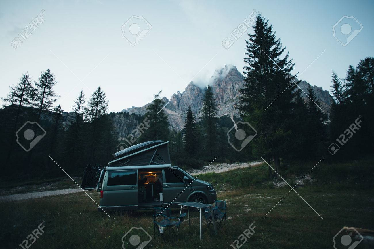Small travel vehicle camping van or big car with folding rooftop with bed is parked on secluded wild site under huge mountain formation in dolomites, surrounded by forest - 86971707