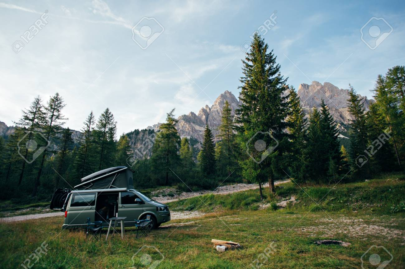 Small travel vehicle camping van or big car with folding rooftop with bed is parked on secluded wild site under huge mountain formation in dolomites, surrounded by forest - 86878086