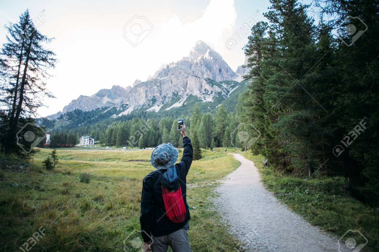 Young urban adventurer with small light backpack stands on path of beginning of hiking trail and makes photo of amazing epic mountain peak in middle of forest - 86878089